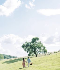 Engaged Couple walking in meadow